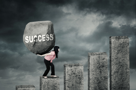 Picture of a female entrepreneur climbing a financial chart while carrying a big rock with Success word Stock Photo