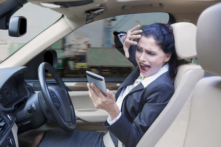 exporter: Portrait of a young Indian businesswoman driving a car while using a mobile phone and looks closing her face before car accident Stock Photo