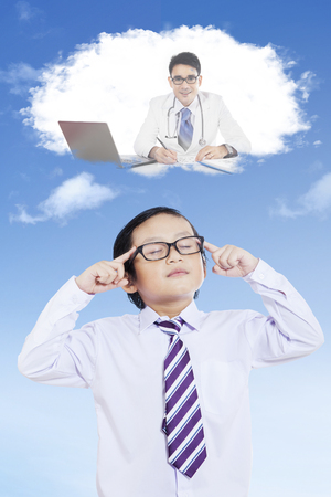 Closeup of elementary student thinking with eyes closed while imagining as a doctor