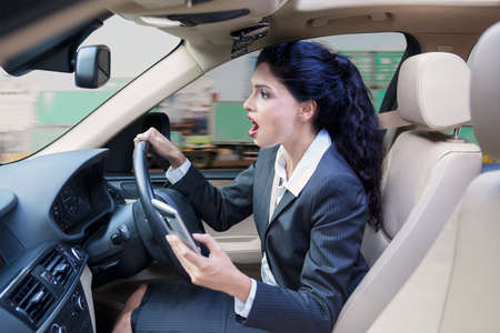 exporter: Indian businesswoman driving a car while using a mobile phone and looks shocked staring at the road
