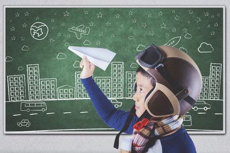 asian children: Photo of a male elementary school student playing a paper plane in the class while wearing helmet and scarf Stock Photo