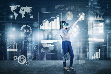 Zakenvrouw werken met digitaal scherm terwijl virtuele glansbril wordt gedrukt en op virtuele knop drukken