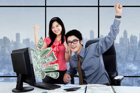 profit celebration: Portrait of two workers earn money online while looking at the camera with happy expression Stock Photo