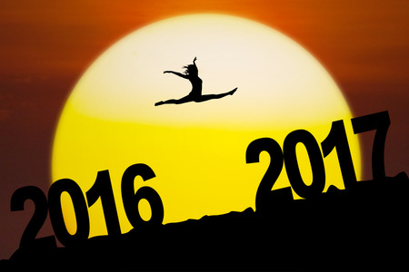Silhouette of an attractive woman is dancing and jumping between numbers 2016 to 2017 on the hill with sundown