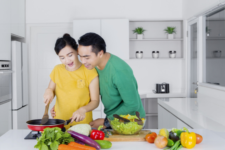 young wife: Young man looking at his wife cooking vegetables with frying pan in the kitchen at home Stock Photo