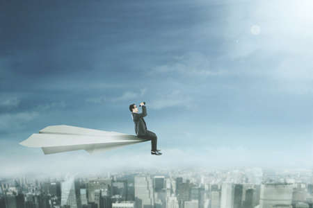 using binoculars: Male entrepreneur sitting on a big paper plane while using a binoculars and flying above a city