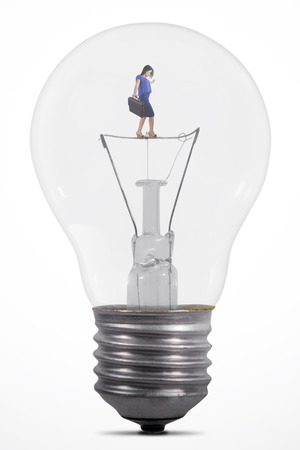 equilibrium: Young businesswoman walking carefully inside a big light bulb while carrying a briefcase, isolated on white background