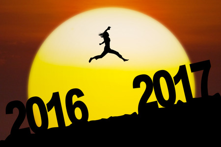 Silhouette of young woman running and jumping between numbers 2016 to 2017 in the sunset Stock Photo