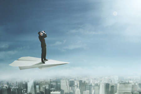 Young businessman flying on a big paper plane while using a binoculars above a city photo