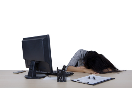 Image of young businesswoman is sleeping in the studio while working with a computer and paperwork on the desk