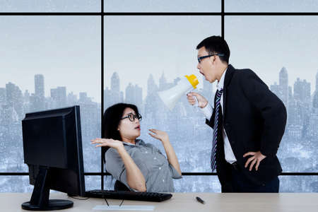 reprimanding: Picture of young male manager looks angry while shouting at his secretary through megaphone in the office