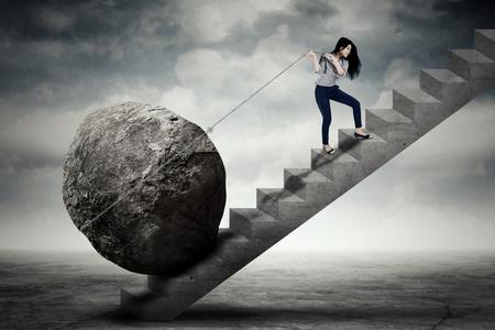 階段の上のチェーンが大きな石を運ぶ美しい女性起業家のイメージ