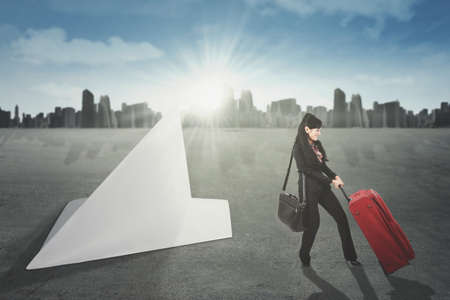 Picture of a female entrepreneur pulling a suitcase toward a big paper airplane. Concept of business travel photo