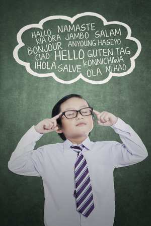 Closeup of young little businessman concentrating with eyes closed while learning multilingual in the classroom