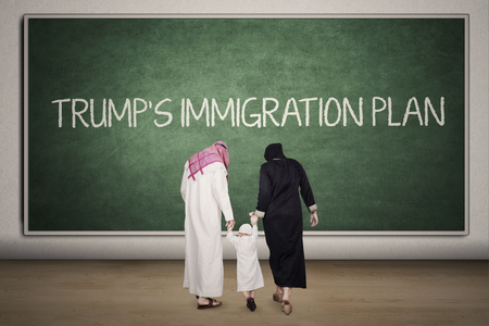 skepticism: Arabian family walking into the classroom with Trumps Immigration Plan word on the chalkboard