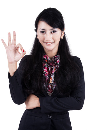 Happy businesswoman making an ok sign - isolated over a white background photo