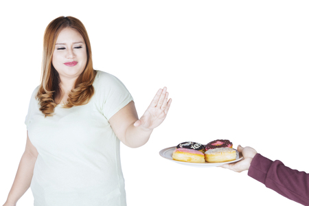 offered: Image of overweight woman refuses donuts offered from someone while standing in the studio