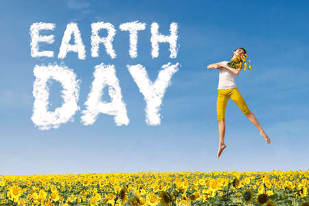 Young woman holding flowers and jumping above sunflower garden with cloud shaped Earth Day text. Earth Day concept photo
