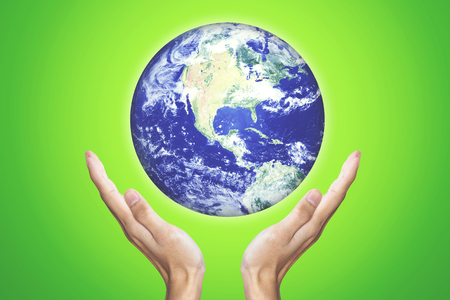 Earth Day concept. Male hands holding a globe with green screen background. Elements of this image furnished by NASA Stock Photo