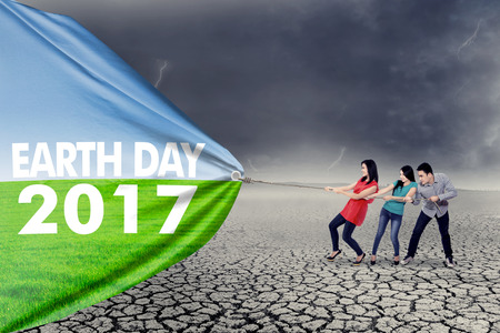 Earth Day 2017 concept. Three people pulling a big banner with text of Earth Day 2017 photo
