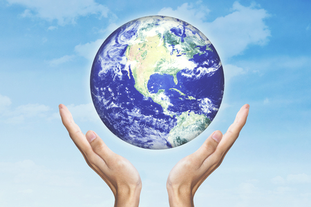Earth Day concept. Human hands holding a globe with sky background. Elements of this image furnished by NASA Stock Photo
