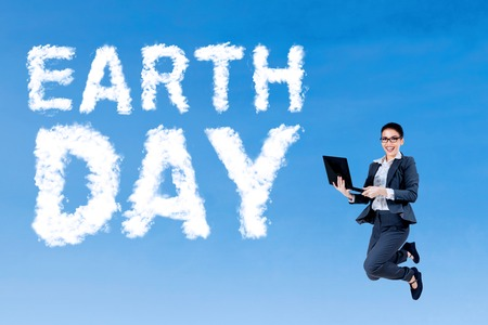 Earth Day concept. Female entrepreneur holding a laptop and jumping on the sky with cloud shaped Earth Day text photo