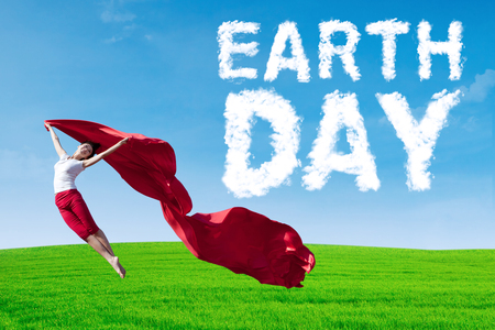 Young woman with Earth Day text on the sky, jumping on the green meadow while holding a red fabric photo
