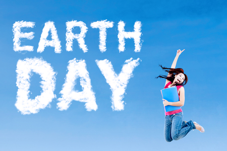 educacion ambiental: Mujer estudiante universitario saltando en el cielo con la nube en forma de texto del Día de la Tierra. Concepto del Día de la Tierra