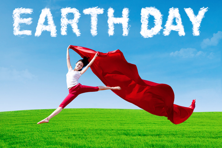 Earth Day concept. Young woman jumping on the meadow while holding a red fabric with cloud shaped Earth Day text photo