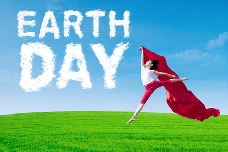 Picture of cloud shaped Earth Day text on the sky, shot with woman jumping on meadow while holding a red fabric. photo