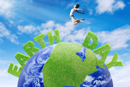 Earth Day concept. Happy woman jumps above a globe with green Earth Day text photo