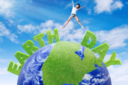 Earth Day concept. Young woman jumping above a globe with green grass and Earth Day text photo