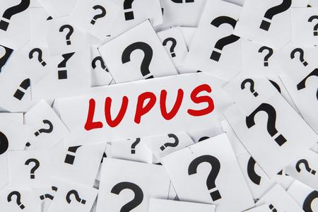 Close-up van vraagtekens en Lupus woord. Concept Lupusziekte Stockfoto