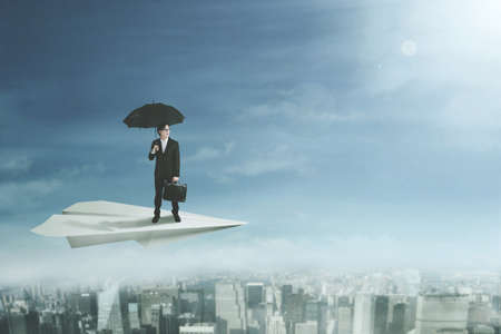 Young businessman standing on a paper plane while holding a briefcase and an umbrella photo