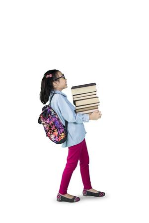 Imagen de niña llevando pila de libros mientras caminaba en el estudio, aislado en fondo blanco