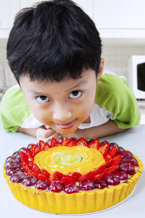 devouring: Photo of cute little boy looks hungry with a strawberry pie in the kitchen at home Stock Photo