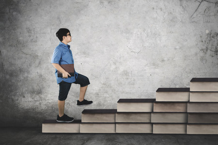Image of cute student walking on books stair while holding a textbook, concept study hard
