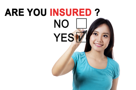 insurer: Portrait of young Asian female using a pen while answering a yes option with a question of are you insured on the whiteboard