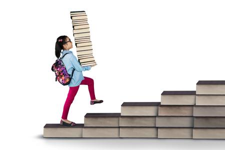 levantar peso: Cuadro de estudiante de primaria llevar pila de libros al caminar en los libros de la escalera, aislado en fondo blanco