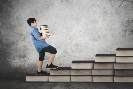 Picture of schoolboy carrying pile of books while walking on staircase, concept of study hard