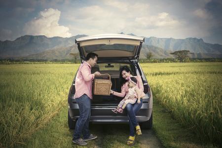 mom dad: familia feliz celebración de la cesta de picnic mientras se está sentado detrás del coche en campo de arroz
