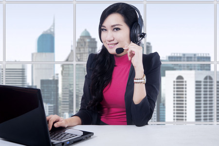 Portrait of beautiful customer service operator working in the office with laptop and headphones Stock Photo