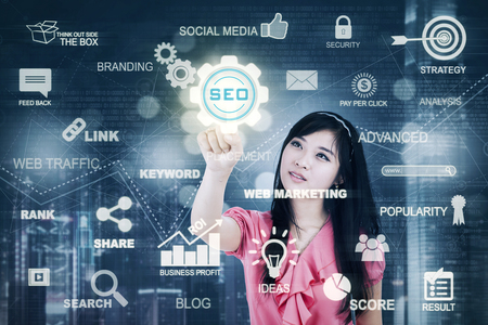keywords link: Pretty Asian businesswoman pressing SEO button on a digital screen. Concept of Search Engine Optimization
