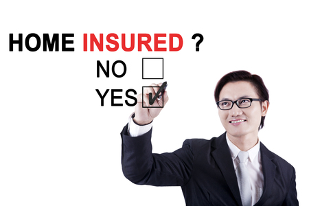 Young businessman using a pen while selecting a yes option with a question of home insured on the whiteboard photo