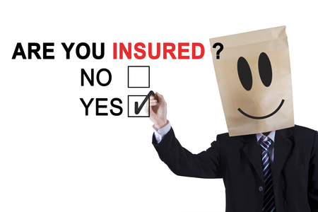 agreeing: Male worker wearing cardboard on his head and holding a pen while agreeing about a question of are you insured