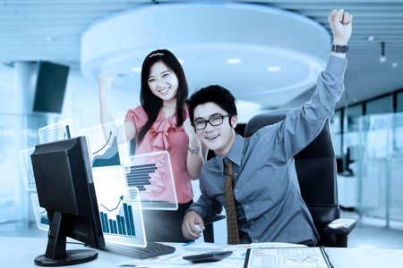 stratification: Portrait of two young workers smiling at the camera with virtual growth charts on the computer screen while raising their hands in the office