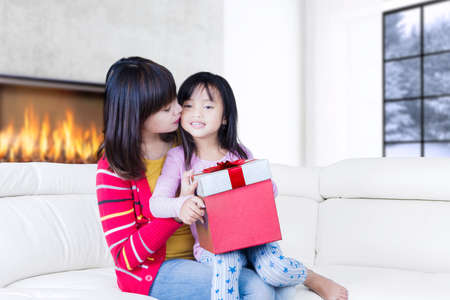 red sofa: Portrait of young mother kissing her child cheek while sitting on the couch with gift box