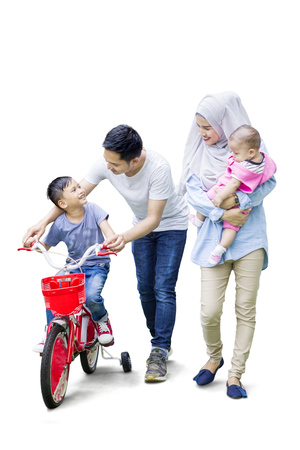 Full length of two muslim parents teach their son to ride a bicycle while the mother holding her baby Zdjęcie Seryjne