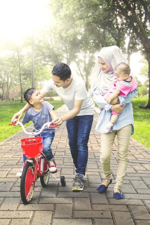Portrait du petit garçon apprend à faire du vélo avec sa famille sur le parc alors que sa mère tenant un bébé Banque d'images - 76680439