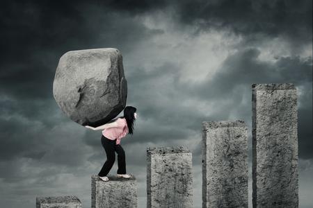 Vrouwelijke ondernemer het beklimmen van een financiële grafiek terwijl het dragen van een grote steen op haar rug met bewolkte hemel
